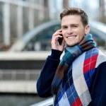 Handsome man using mobile at bridge railing — Stock Photo