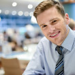 Smiling young man relaxing in restaurant — Stock Photo