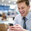 Happy young executive sitting with smartphone — Stock Photo
