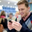 Young man in cafe and using his mobile phone — Stock Photo #45014021