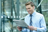 Handsome businessman reading a newspaper — Stock Photo