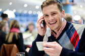 Young man using mobile phone in cafe — Stock Photo