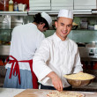Young chef making pizza at kitchen — Stock Photo