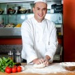 Smiling chef preparing pizza base — Stock Photo