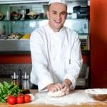 Smiling chef preparing pizza base — Stock Photo