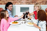 Happy family in a restaurant clinking their glasses — Stock Photo