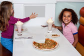 Little girls enjoying pizza in a restaurant — Stock Photo