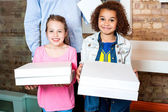 Kids holding pizza boxes — Stock Photo