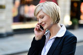 Corporate lady using her phone — Stock Photo