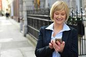 Businesswoman using her smart phone — Stock Photo