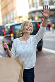 Casual woman hailing a taxi cab — Stock Photo