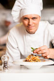 Chef arranging pasta salad in a white bowl — Stock Photo