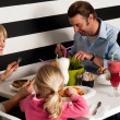 Family of four having meal in restaurant — Stock Photo