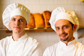 Young smiling chefs posing in bakery — Stock Photo