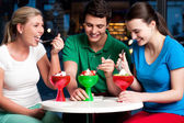 Cheerful friends enjoying tempting dessert — Stock Photo