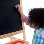 Girl writing on classroom chalkboard — Stock Photo #49223913
