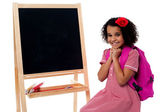 School kid sitting near blackboard — Stock Photo