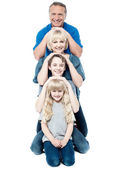 Family of four posing in a row — Stock Photo