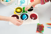 Human hand coloring eggs — Photo