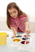 Girl coloring eggs — Stock Photo
