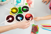 Hands dying easter eggs — Stockfoto