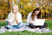 Girls study in autumn park — Stock Photo