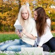 Girls study in autumn park — Stock Photo