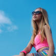 Portrait of beautiful blonde girl in sunglasses on background blue sky — Stock Photo #28640431