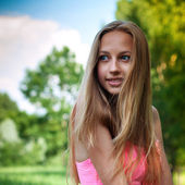 Portrait of a beautiful young girl against blue sky with clouds — Stock Photo