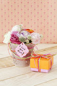 Beautiful bouquet in flowerpot and a gift box for Mother's Day — Stock Photo