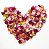 Heart of rose petals with the words: love you — Stock Photo