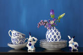 Still life with blue and white dishes and flowers in a little va — Stock Photo