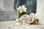 Old white fake flower on grave — Stock Photo