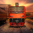 Постер, плакат: Train passing by in orange sunset