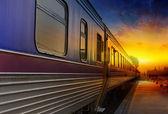 Tren turuncu günbatımı geçirerek — Stok fotoğraf
