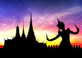 Thai dance perform by young woman silhouetted with temple in thailand background — Stock Photo