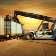 Crane lifting up container in sunset — Stock Photo