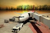 Letadlo na letišti na načítání při západu slunce — Stock fotografie