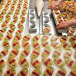 A baker brushes egg yolk on cakes — Stock Photo #42001523