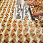 A baker brushes egg yolk on cakes — Stock Photo