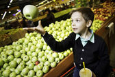 A boy buys apples at the supermarket — Stock Photo