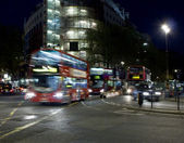 Double deckers driving through crossroads in London, England — ストック写真