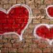 Red hearts painted on a brick wall — Stock Photo