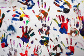 Colorful handprints hands on a white canvas — Stock Photo
