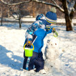 Little boy with snowman — Stock Photo