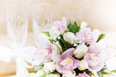 Wedding bouquet and wine glasses in the background — Stock Photo