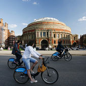 Tourists on rental bike, passing by Royal Albert Hall — Stock Photo