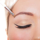 Eye closeup with make-up and brow brush — Stock Photo