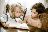 Portraits of young childs reading a book — Stockfoto