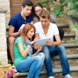 Laughing teenagers looking at the touchpad screen outdoors , Ita — Stock Photo